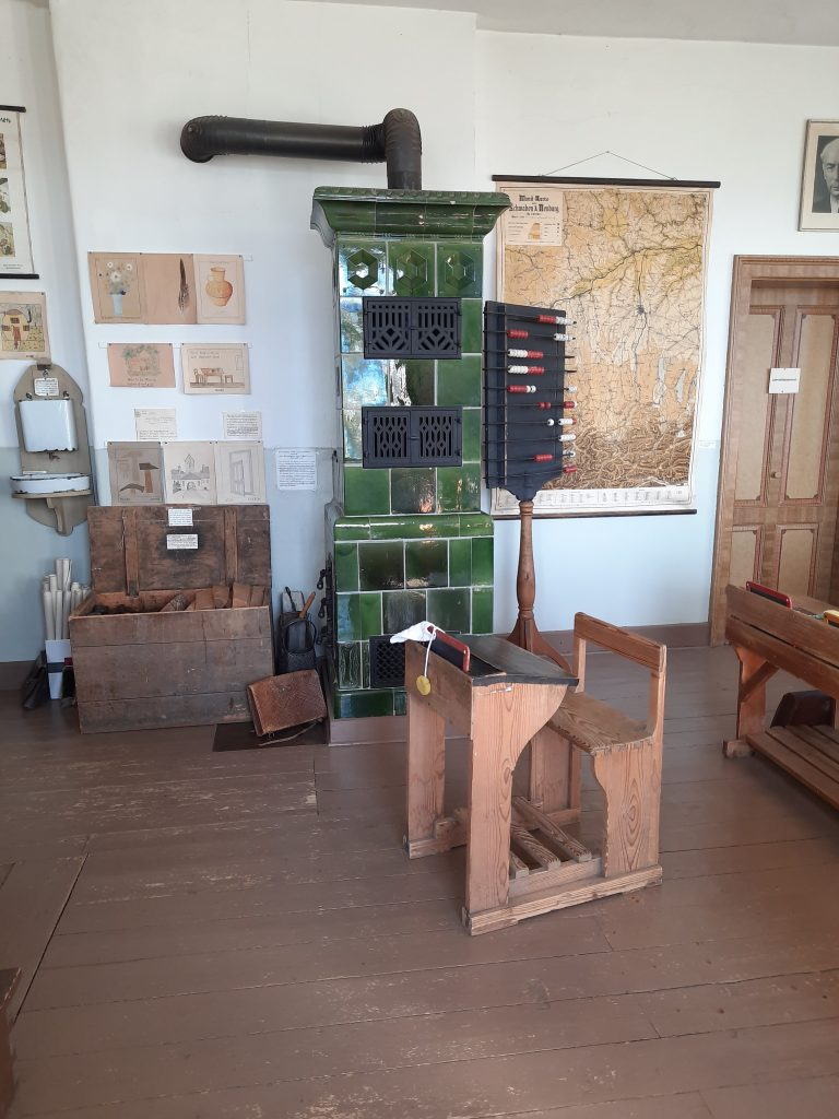Bild vom Einzeltisch, dem Heizofen und der Feuerholzkiste